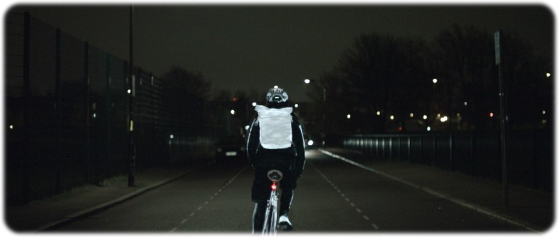 A single cyclist riding at night with the life paint on his bike,shoes,helmet and backpack