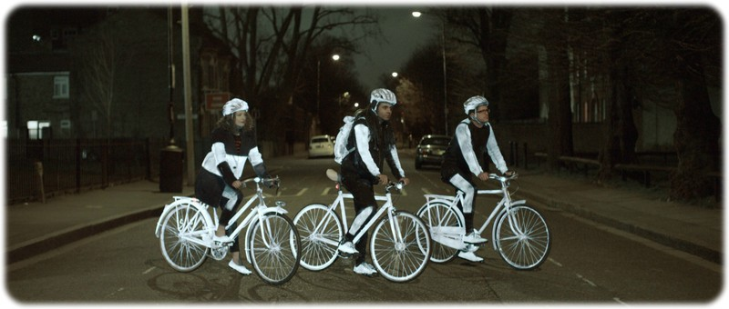 Three cylist all sat on their bike at night with the reflective life paint on thier bikes,shoes,helmet and clothes