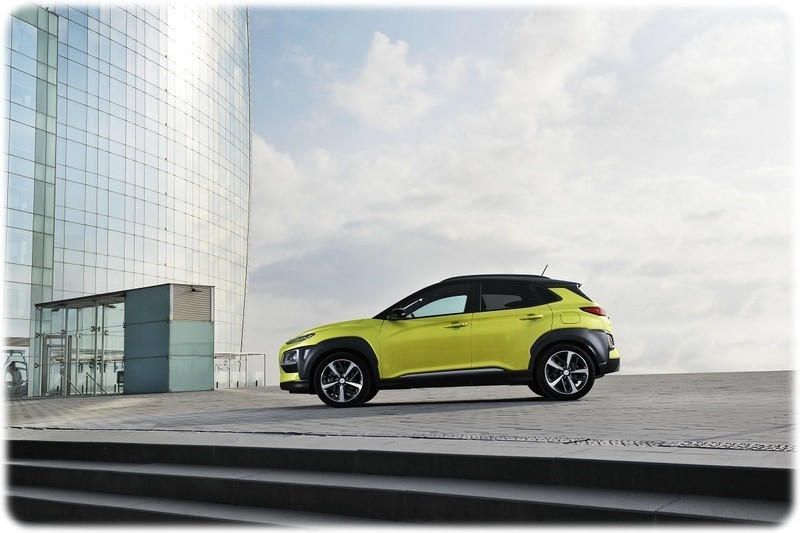 2018 Hyundai Kona in Acid Yellow, in fornt of a large modern glass building