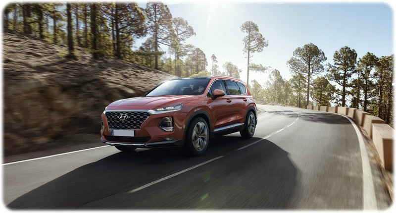 New 2018 Hyundai Santa Fe on the road driving front view in a red colour.